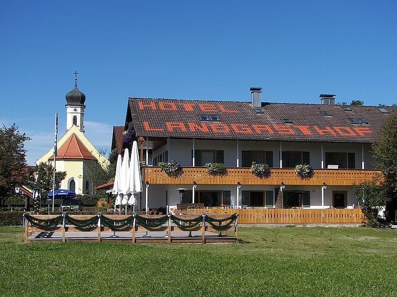 Aussenansicht Hotel und Landgasthof Schöntag mit Balkonen und Kirche St Heinrich am Starnberger See Fünfseenland, Bayern, Deutschland