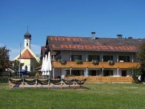 Aussenansicht des Hotels mit Blick auf die Balkone und den Biergarten des Landgasthofs Hotel Schöntag in St. Heinrich am Starnberger See, Oberbayern, Deutschland