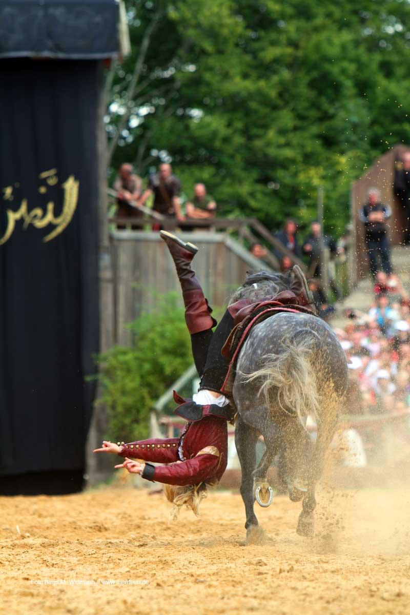 Stunt auf dem Pferd in der Arena des Kaltenberger Ritterturniers